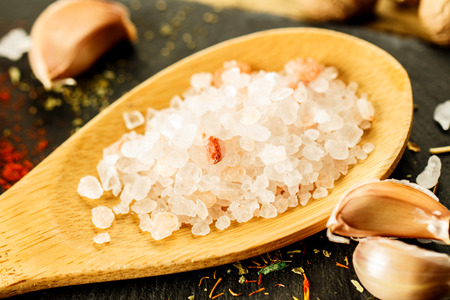 The Himalayan pink salt. Food, large salt in a wooden spoon. Stock Photo