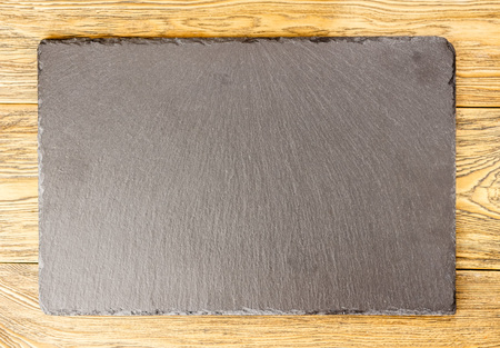 Serving Board. Dish for filing, stone slate. Restaurant menu. Place for Your text. The view from the top. Slate Board on wooden background. Lettering with chalk.