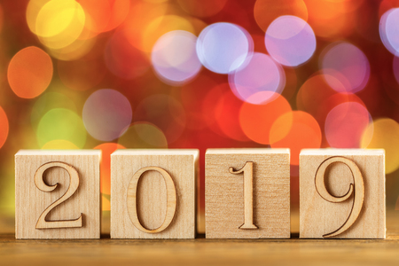 Christmas card, wooden cubes on the background of bokeh. Catchy bright design. Happy new year 2019.