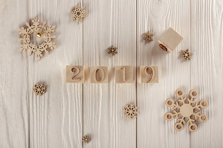 Christmas card, wooden cubes on a wooden background. Home cozy design. Happy new year 2019.