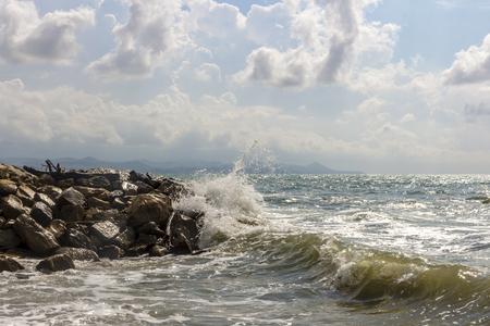 Waves crashing against rocks. Light storm. Seascape. Cloudy sky.