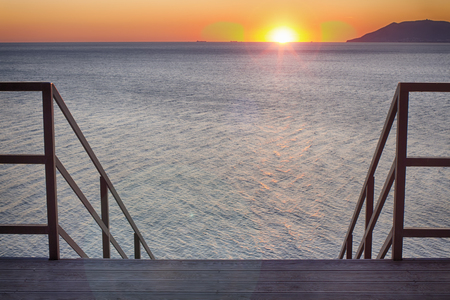 Stairs leading into the sunset. Seascape, lens flare 35 mm. Stok Fotoğraf