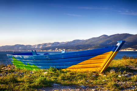 Bright decorative rowing boat. Seascape, mountain range on the horizon.
