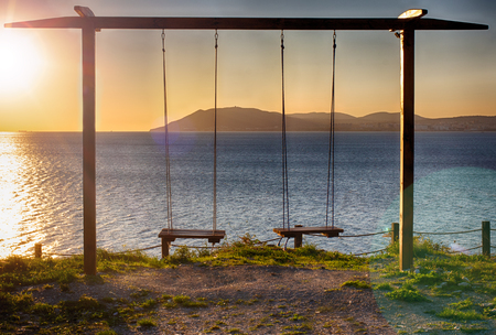 Rope swing at sunset. A place of romantic encounters. Swing on cliff. Setting sun. Seascape. Stok Fotoğraf
