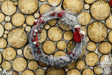 Holiday wreath made of twigs. New year and Christmas. Background of wooden ends. Made by hand in the village. Rustic style.