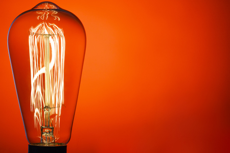 Vintage light bulb, on bright red background. Abstract composition. Old style. IDEA!!! Place for Your text. Stok Fotoğraf