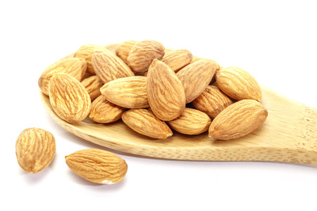 Almond on white background. Isolated objects. Nuts, natural product. Vegetable protein. Nut in a wooden spoon. Close up. 写真素材