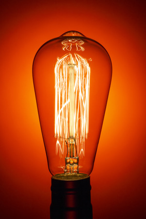 Vintage light bulb, on bright red background. Abstract composition. Old style.