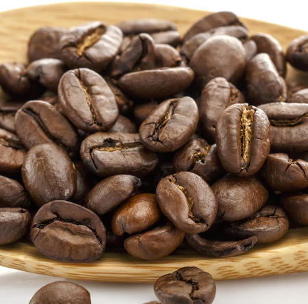 Coffee Beans. Close-up, clear grain structure. Coffee on a wooden spoon.