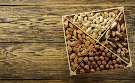 Assorted nuts. Set of nuts top view. Wooden table top. Texture background. Place for advertising text. 写真素材