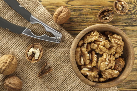 Walnut, shell cleaning process. Natural product on a wooden table. Rustic style.