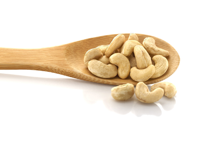 Cashew nut, on wooden spoon, isolated on white background.