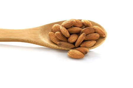 Almond in a wooden spoon. Isolated on white background. Place for Your text.