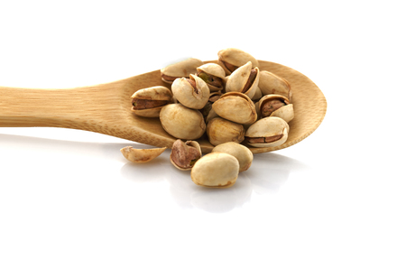 Pistachio, on a wooden spoon. Isolated on white background. Place for text.