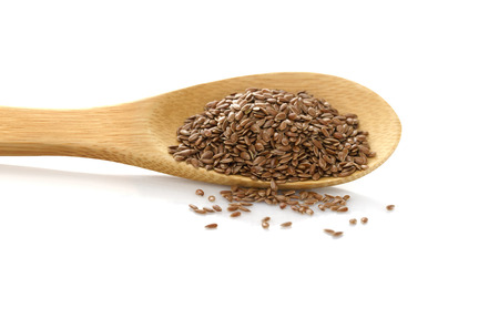 Flax seed. Linen in wooden spoon on white isolated background.