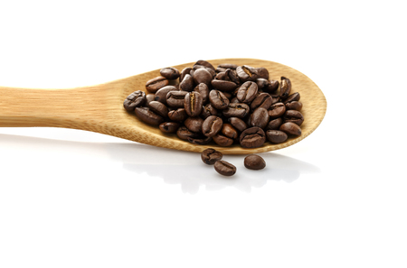 Coffee beans in spoon. Roasted coffee beans. On a white background isolated. Stok Fotoğraf