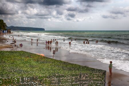 Russian resort. Golden Sands beach. 16.09.2018 21.32 pm Easy the storm allows vacationers to swim. Prohibiting swimming sign in Russian.