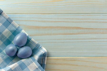 Happy Easter. Colored eggs on a towel in a cage. Wooden background, rustic style. Egg hunt.