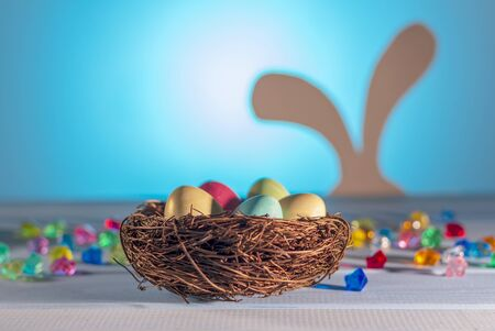 Easter nest, hidden eggs by a hare.  Easter Bunny on a blurry background. Spring religious holiday. Colored Easter eggs.