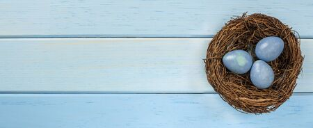 Easter eggs in nests, wooden blue background. Easter mood, holiday card. A place to write text.