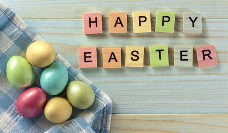 Happy Easter, Easter eggs on a wooden blue background, rustic style. Wooden colored letters. Ready congratulations. Quail egg. The view from the top.