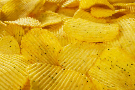 Potato fluted chips with spices, natural product close-up. Delicious background. Text on top of the image. Fast food.