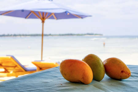 Mango on the table, beach dessert. Chilled fruit. Tonic food.