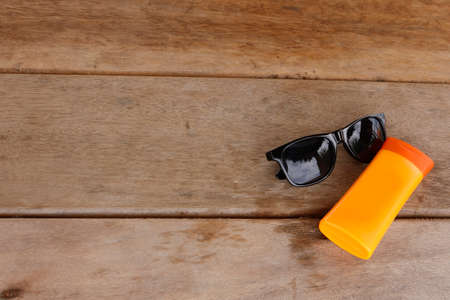 Beach kit. UV protection. Glasses and sunscreen for safety in the sun. Space for the text. Foto de archivo