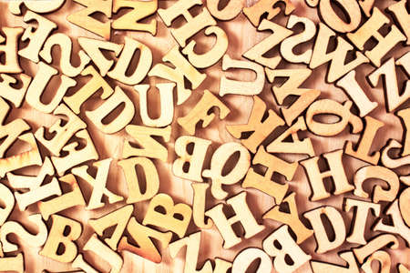 English alphabet. Wooden letters on a wooden background. A letter mess.