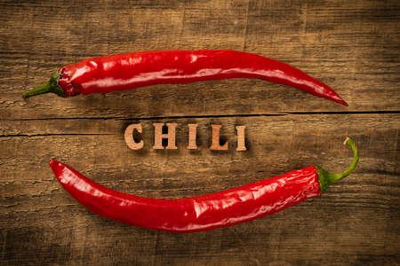 Chili Pepper on a wooden table. Rustic style in a low key. Lettering in wooden letters.