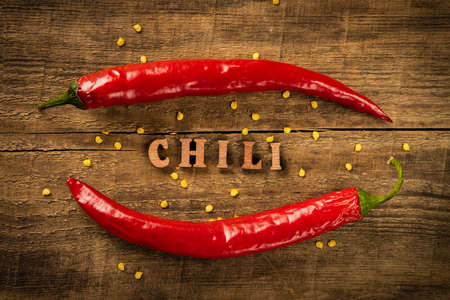Chili Pepper on a wooden table, pepper seeds. Rustic style in a low key. Lettering in wooden letters. Foto de archivo