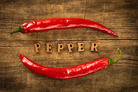 Chili Pepper on a wooden table,. Rustic style in a low key. Lettering in wooden letters.