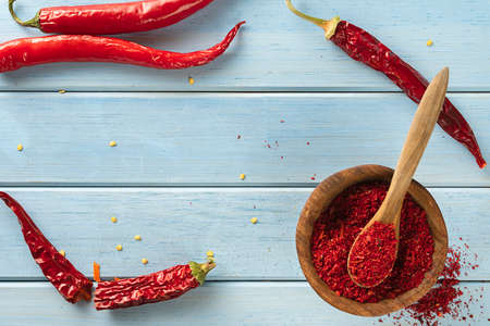 Red pepper paprika, on a blue wooden background. Top view, space for text.
