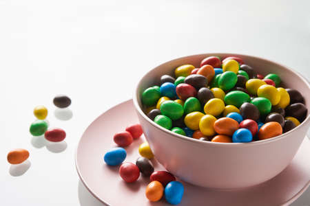 Bright candy drops in a pink bowl. Festive mood.