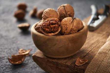 Walnuts in a bowl. The process of splitting nuts. Rustic style. Foto de archivo