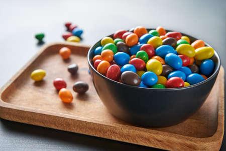Bright candy drops in a black bowl on a wooden tray. Festive mood. Foto de archivo
