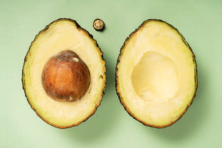 Avocado Hass cut in half. Top view. Healthy food. Fruit on a green background.
