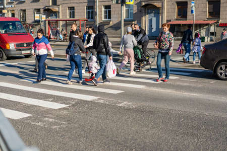 Saint Petersburg Russia 28.05.2021 pm 19.00. The intersection of Revolution Highway and Sredneokhtinsky Prospekt. A group of people crosses the road at a green traffic light.