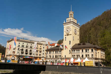 Rosa Khutor. The clock tower on the central square. Town hall. People walk around the square. Russia Sochi Rosa Khutor. Редакционное