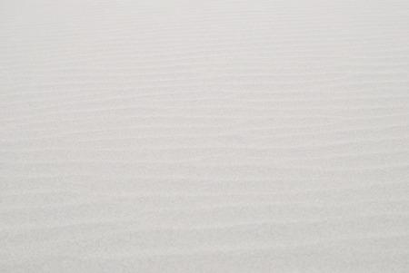 Blurred wavy white sand texture, dry nature background