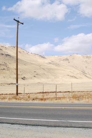 Roadtrip view with a road and dry sandy hill, California, USA Stok Fotoğraf