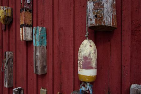 Old retro lobster buoys hunged on the red wall, horizontal postcard New England 스톡 콘텐츠