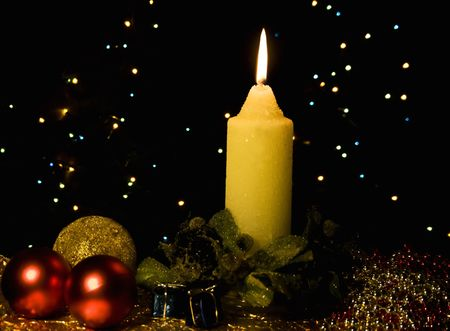 Burning candle with Christmas-tree decorations against a dark background photo