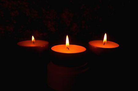 threw: Three candles against a dark background