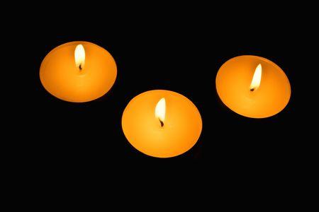 Three candles against a dark background photo