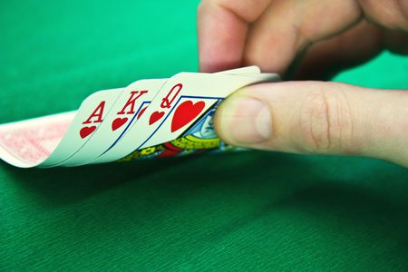 Playing cards and fingers on a green background