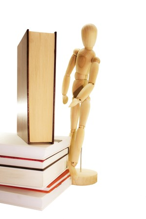 Closed books and wooden dummy isolated on a white background photo