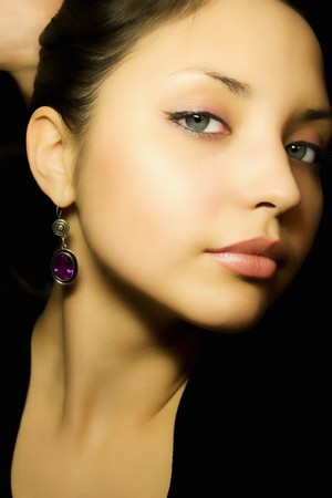 Portrait of a young beautiful girl with earrings photo