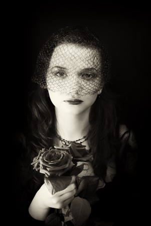 portrait of woman in the veil with a bouquet of roses photo
