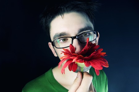 young guy with a red flower on a black background 版權商用圖片